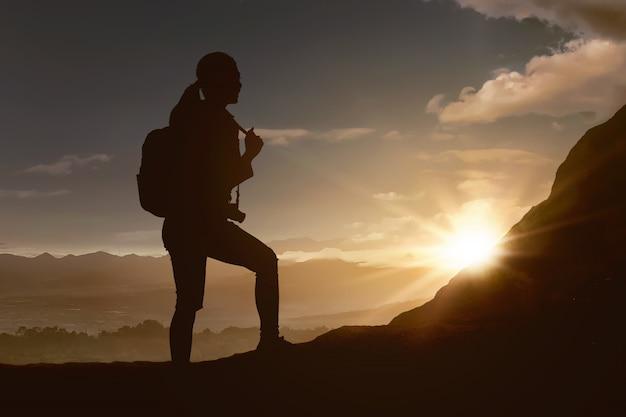Silhouet van reizigersvrouw die de berg wandelen