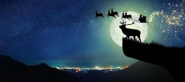 Silhouet van rendieren die op een klif staan en de kerstman die op hun rendieren over de volle maan vliegt