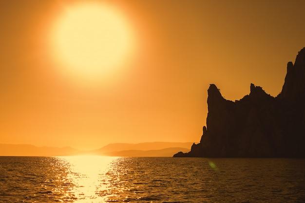Silhouet van rode zee bergen op zonsondergang achtergrond