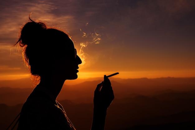Silhouet van rokende vrouw in zonsonderganglandschap