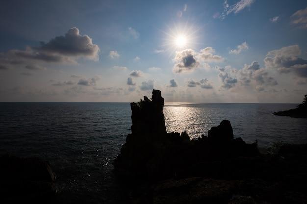 Silhouet van rots in het midden van de oceaan met de zon.