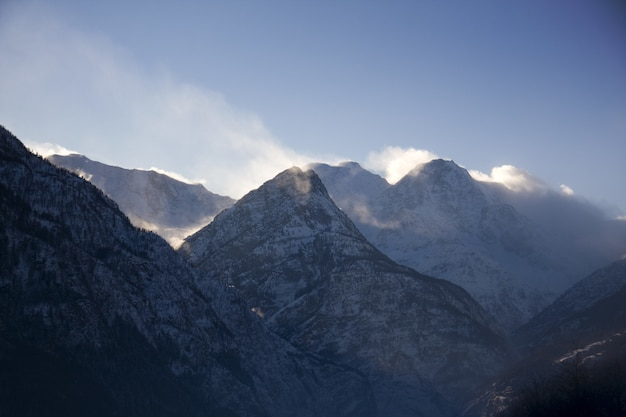 Silhouet van rotsachtige bergen bedekt met sneeuw en mist tijdens de winter