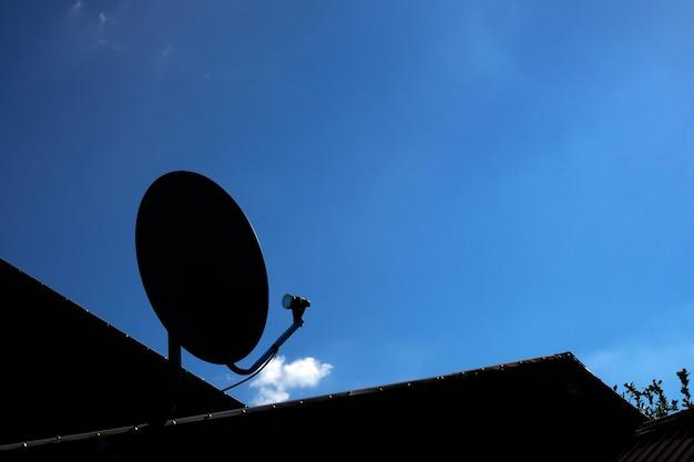Silhouet van satellietschotel met blauwe hemel