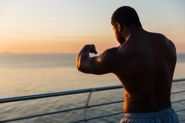 Silhouet van serieuze jonge atleet die buiten bokst bij zonsopgang