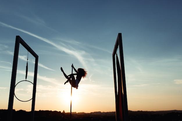 Silhouet van sexy pooldanser die op dak bij zonsondergang presteren
