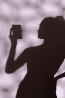 Silhouet van sierlijke vrouw die een selfie neemt