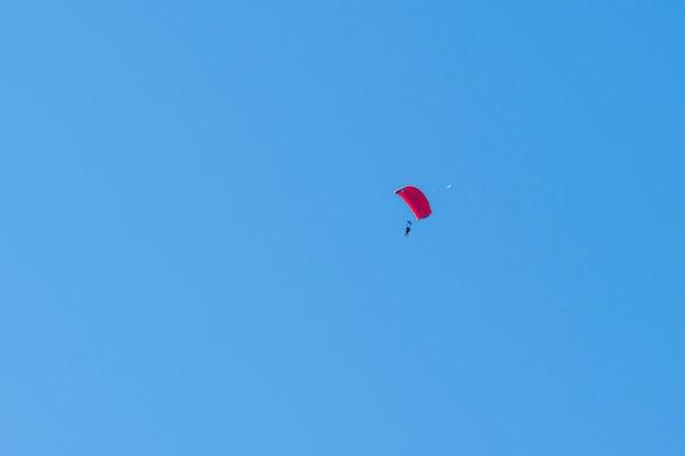 Silhouet van skydiver vliegen in blauwe heldere hemel.