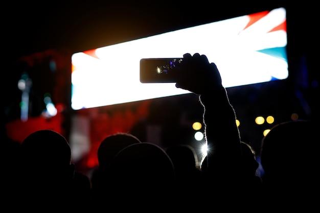 Silhouet van smartphone in handen van ventilator tijdens muziekshow