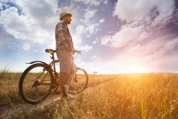 Silhouet van sport persoon fietsen op het veld op de prachtige zonsondergang