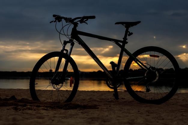 Silhouet van sportfiets op een strand. zonsondergang.