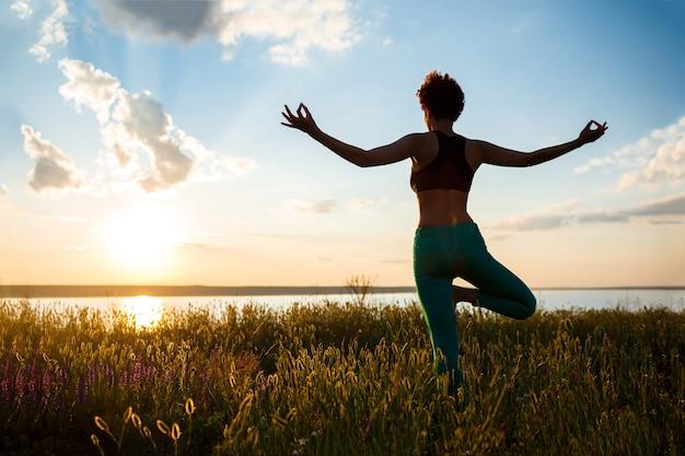 Silhouet van sportieve meisje beoefenen van yoga in veld bij zonsopgang.