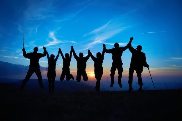Silhouet van springende vrienden in zonsondergang tegen blauwe hemel