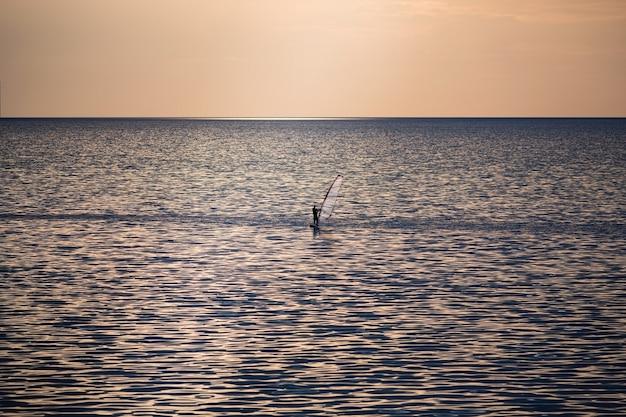 Silhouet van surfer balanceren op windsurfplank. windsurfen, zeilen, watersporten, extreem