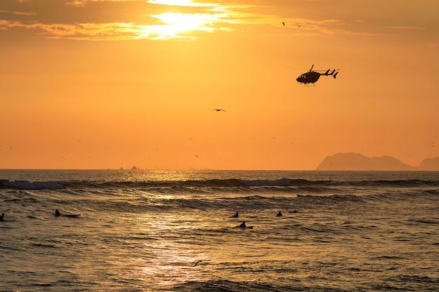 Silhouet van surfers en meeuwen tegen de achtergrond van de ondergaande zon boven de kustlijn van de stille oceaan in lima