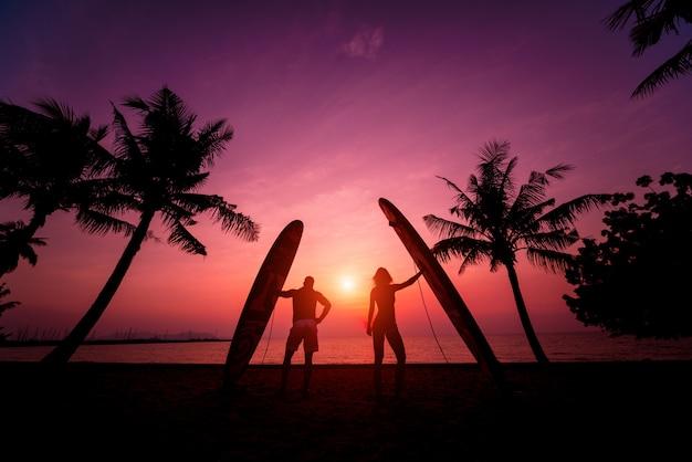 Silhouet van surfers paar houden lange surfplanken bij zonsondergang op tropisch strand