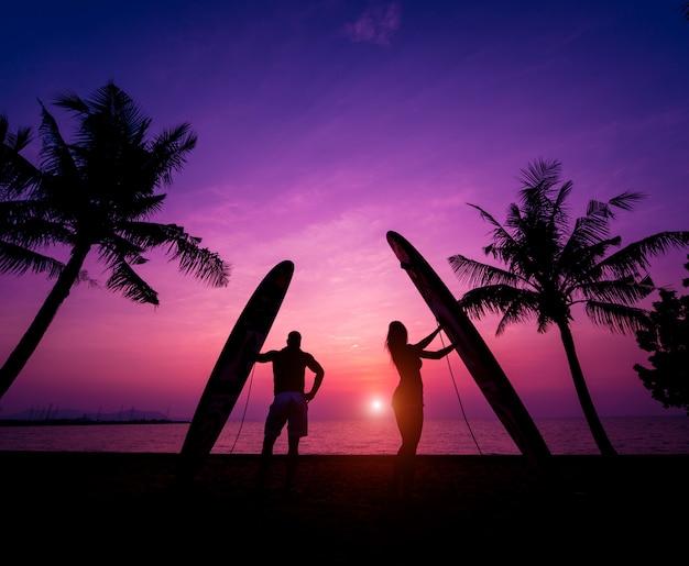 Silhouet van surfers paar houden lange surfplanken bij zonsondergang