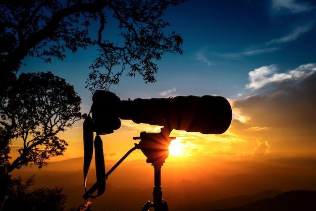Silhouet van telelens boven bergen tijdens de zonsondergang met de hemel van de twee toonzonsondergang