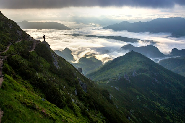 Silhouet van toerist met rugzak op rotsachtige berghelling met opgeheven handen