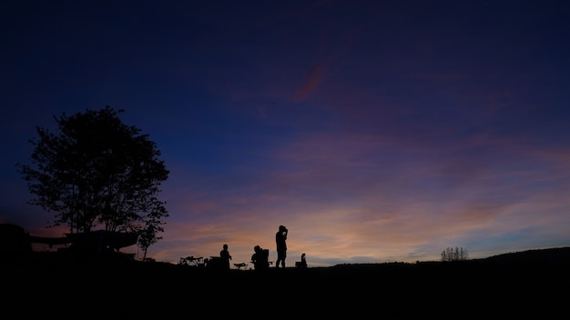 Silhouet van toeristen die in het ochtendlicht kamperen