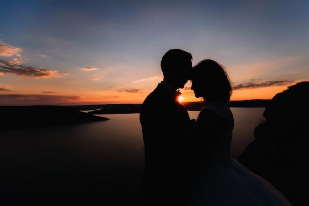 Silhouet van twee kussende mensen. teder kussen bruidspaar