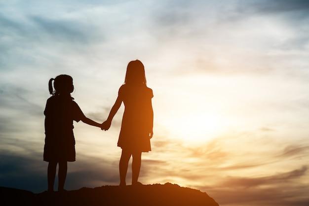 Silhouet van twee meisje met plezier in de natuur