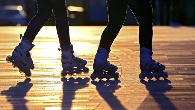 Silhouet van twee paar benen op rolschaatsen. hobby's en entertainment