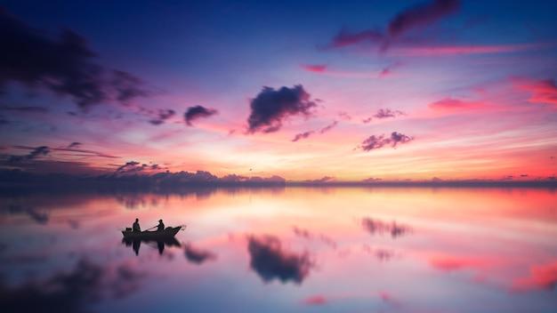 Silhouet van twee personen zittend op de boot overdag