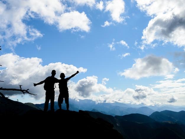 Silhouet van twee vrienden samen op de top van een berg met een prachtig landschap