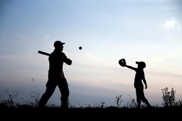 Silhouet van vader en zoon die honkbal spelen op het concept van de natuurfamiliesport