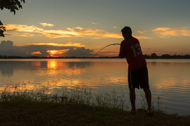 Silhouet van visser die aan rivierkant vissen in zonsondergang