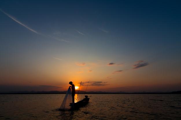 Silhouet van visser die net op het meer werpt