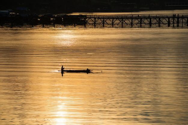 Silhouet van visser en houten brug
