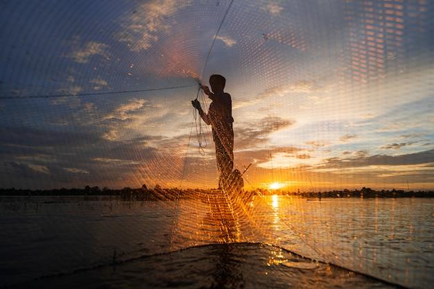 Silhouet van visser op vissersboot met netto op het meer bij zonsondergang, thailand