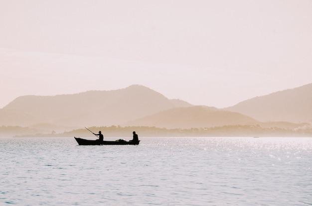 Silhouet van vissers in een kleine boot