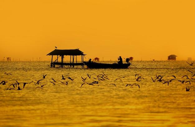 Silhouet van vissersboot met hut op zee zonlicht met vliegende zeemeeuw in landschaps gouden hemel