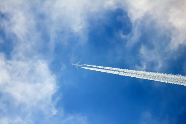 Silhouet van vliegtuigen die in de wolken vliegen en contrail verlaten