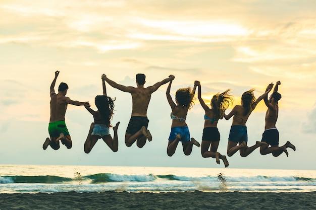 Silhouet van vrienden die op het strand springen