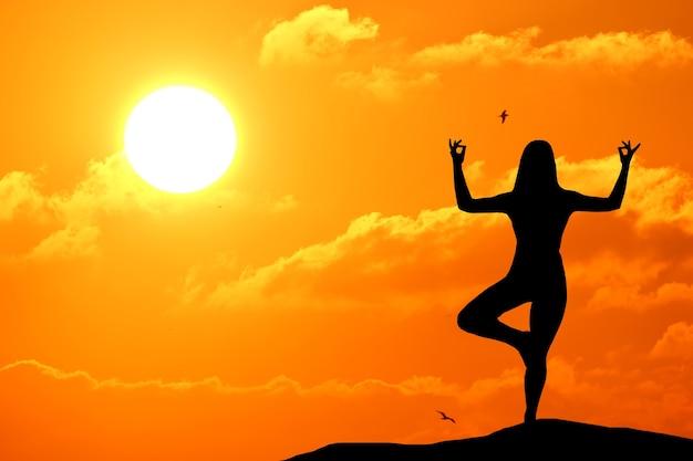 Silhouet van vrouw beoefenen van yoga tijdens zonsondergang aan zee.