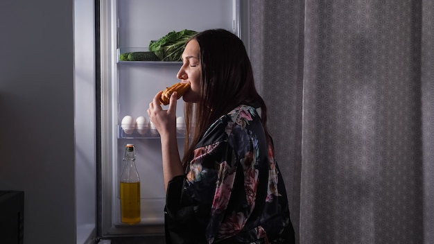Silhouet van vrouw die eclair eet bij koelkast in donkere keuken