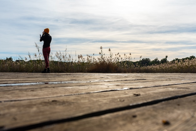 Silhouet van vrouw die een foto met haar neemt mobiel van een mediterraan landschap.