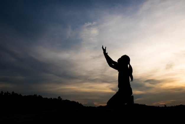 Silhouet van vrouw die met god bidt