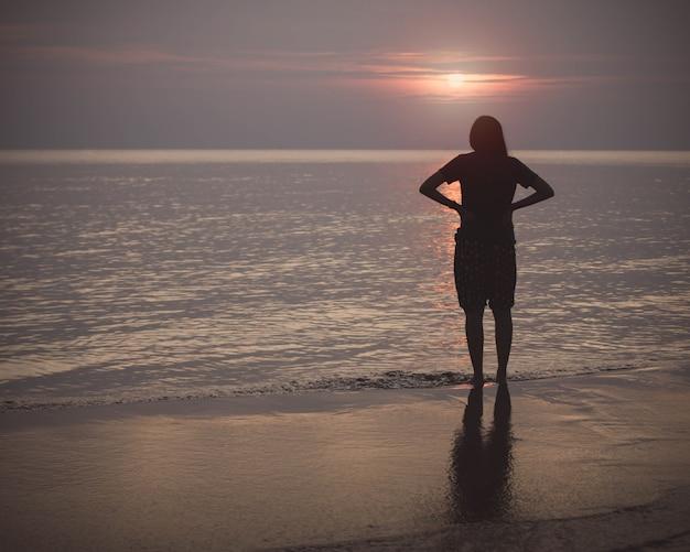 Silhouet van vrouw die op de strandachtergrond lopen met uitstekende filter