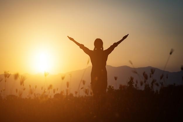 Silhouet van vrouw die over mooie hemelachtergrond bidden