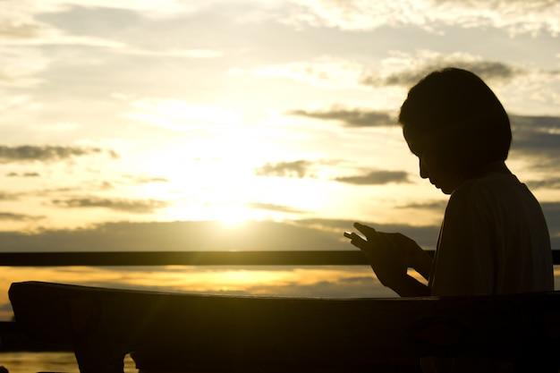Silhouet van vrouw die slimme telefoon over mooie zonsondergangachtergrond gebruiken.