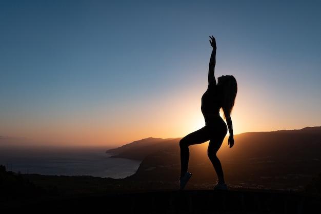 Silhouet van vrouw die van vrijheid geniet die zich gelukkig voelt bij zonsondergang met bergen en overzees