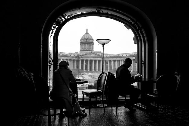 Silhouet van vrouw en man lezingsboeken in een koffie in boekhandel in heilige petersburg, rusland