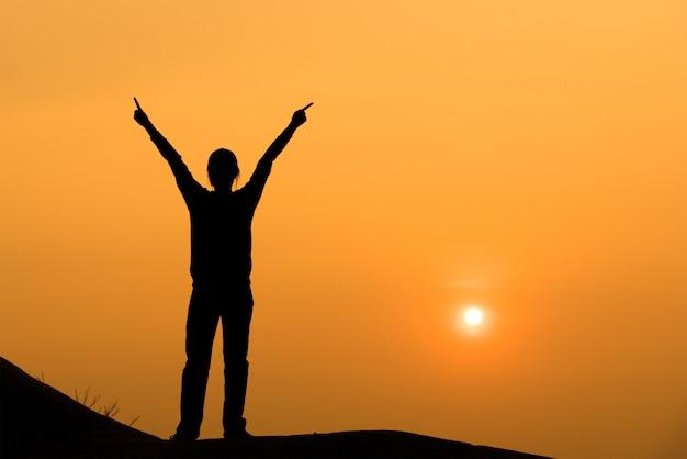 Silhouet van vrouw het uitspreiden van hand aan de hemel