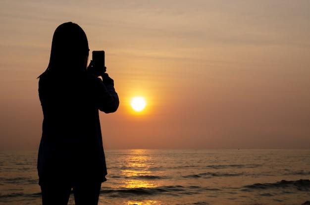 Silhouet van vrouw nemen foto zonsondergang op de zee en kleurrijke lucht door smartphone.