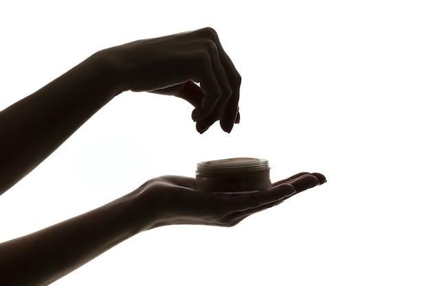 Silhouet van vrouwelijke handen met gezichtspoeder geïsoleerd op een witte achtergrond