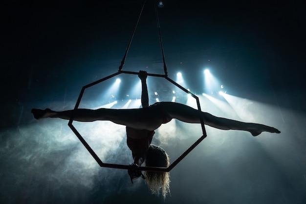 Silhouet van vrouwelijke luchtacrobaat op het podium van het circus met spotlichten